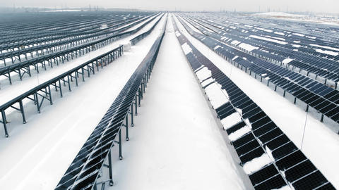 AERIAL: Photovoltaic in winter covered with snow. Solar panels among the snow Footage