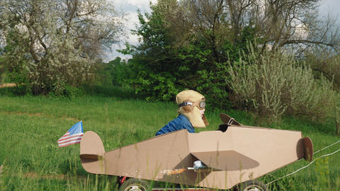 A little boy rides a homemade cardboard plane Footage