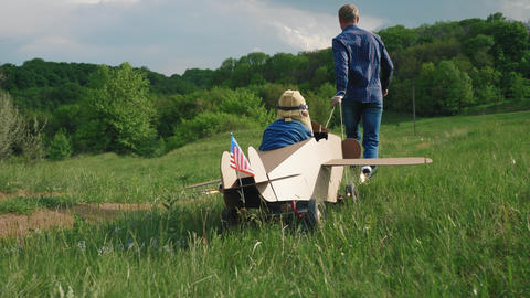 A little boy rides a homemade cardboard plane. Concept of friendly family Footage