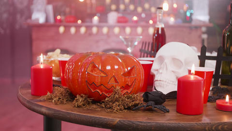 Skull and jack-o-lantern on a wooden table in a halloween decorated pub Footage