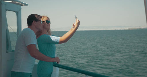 Loving couple making mobile selfie during sea tour Footage