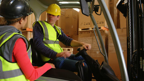 Forklift driver interacting with warehouse worker Live Action