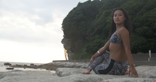 Tanned Asian Japanese girl doing Yoga on rocks beach side 4K Footage