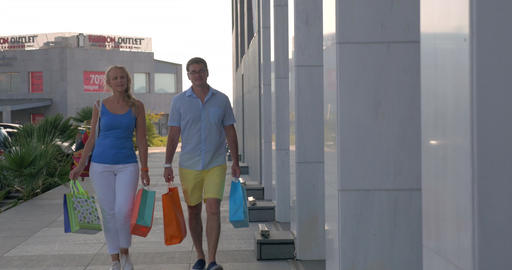 Cheerful couple with shopping bags walking in the city Footage