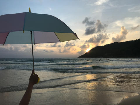 girl is holding a colorful pastel umbrella on the beach with amazing sunset Photo