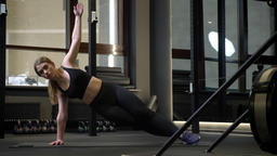 Young sportsgirl standing in side plank with her cellphone lying nearby in gym Footage
