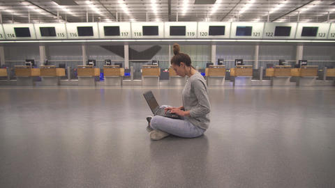 Woman work on laptop and waiting for flight in airport in terminal on the floor Archivo