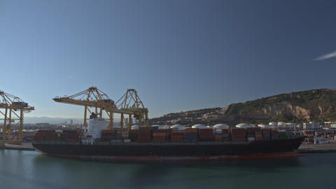 Timelapse of cranes loading cargo ship with containers at industrial port, Spain Archivo