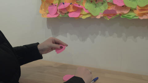 Woman pinning a piece of paper with heart onto the wish board Archivo