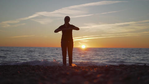 silhouette of a young woman engaged in fitness in nature at sunset, a sports Footage