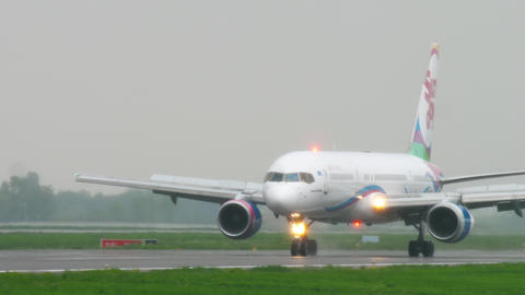 Airplane taxiing after landing at rainy weather Footage