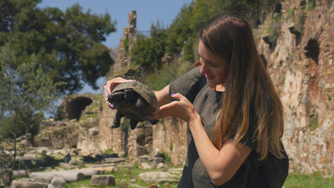 Young woman in green t-shirt holding in hands old tortoise Live Action