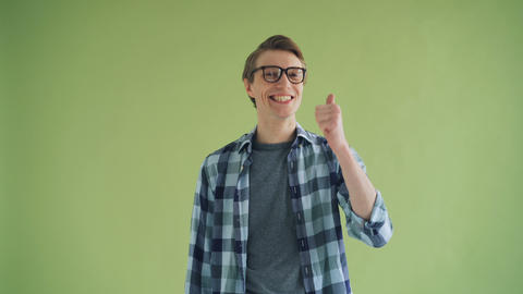 Portrait of cheerful male showing thumbs-up and smiling on green background Footage