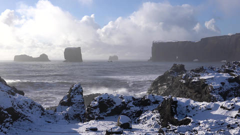 Cape Dyrholaey on a winter day with snow-covered coastline, Iceland Live Action