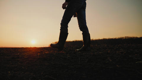 Male farmer in rubber boots walking through cultivated agricultural field Footage