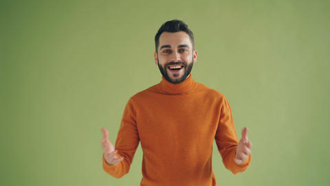 Portrait of happy satisfied man showing thumbs-up smiling on green background Footage