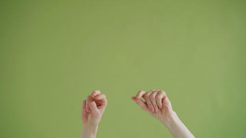 Close-up of hands snapping fingers then moving in rhythm on green background Live Action