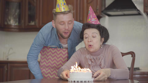 Positive emotional smiling lady sitting at the table holding the small cake with Footage