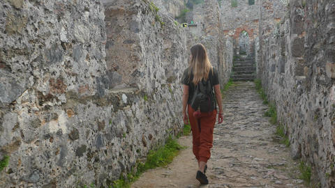 Woman tourist walking on ancient castle wall to shoot a picture with calm Footage