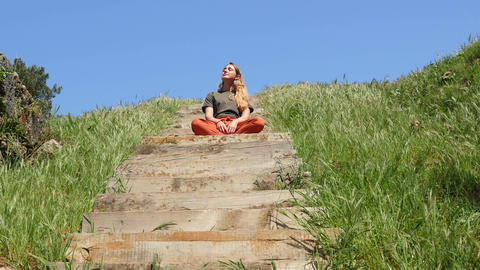 Young caucasian woman sitting on the wooden stair and enjoying life in sunshine Live Action