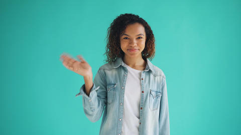 Portrait of friendly woman waving hand and looking at camera with happy face Footage