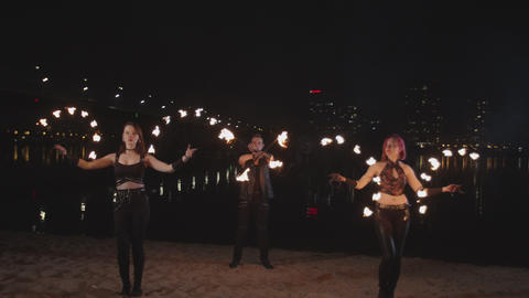 Skillful fireshow artists juggling fire by river Live Action