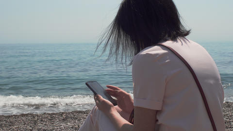 Woman Sitting Near The Sea Relaxing And Using Smartphone GIF