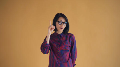 Portrait of clever woman in glasses having good idea raising finger and smiling Footage
