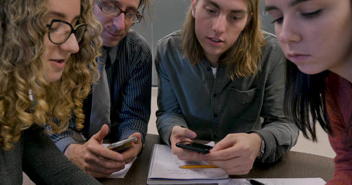 Young woman in her early 20s or late teens sharing information on her smartphone with her teacher Footage