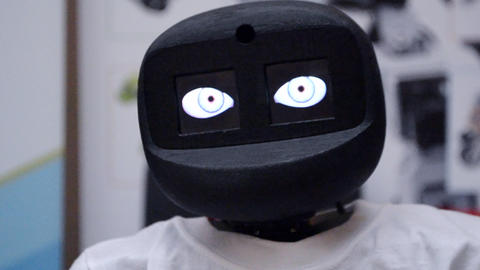 Robot moves its head and blinks its eyes close-up Live Action