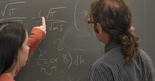 Young woman helping her male professor solve a difficult math formula on a blackboard Live Action