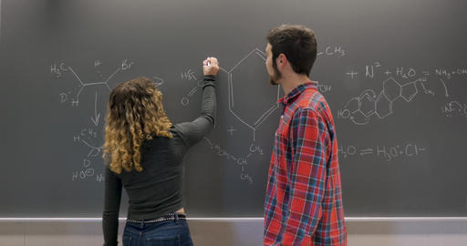 Young female college student explaining a hard chemical formula to a male student using chalk on a Footage