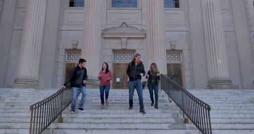 Four classmates including two young men and two young women walking down steps in front of a Live Action