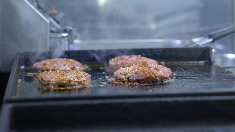 Cooking a hamburger, patty or steak. On a hot stove, a cook fries meat in a Live Action
