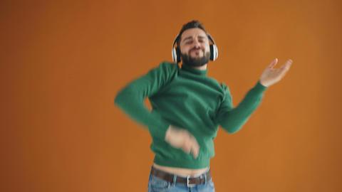 Attractive millennial listening to music through headphones dancing having fun Footage