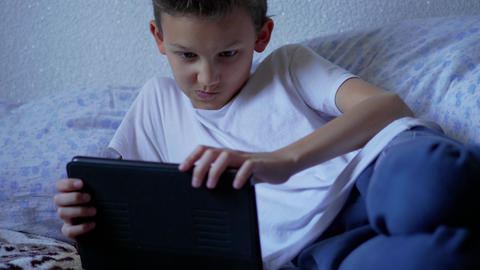 Browsing social network on tablet teenager boy, emotions Footage