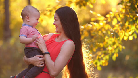 Cheerful mother play with her baby on nature Footage