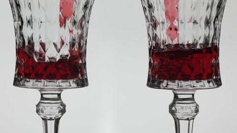 Rose wine. Red wine pour in two wine glasses over white background Live Action