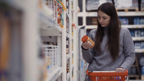 young women buying peanut paste at supermarket Footage