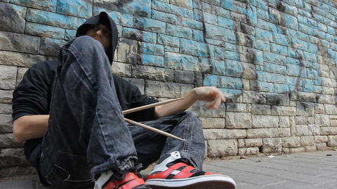 A homeless street performer person drum by the sidewalk Footage