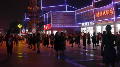 Dancing Chinese people crowd in the square at... Stock Video Footage