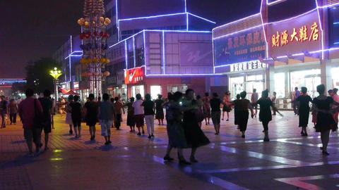 Dancing Chinese people crowd in the square at night.Flashing neon Commercial Str Footage