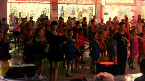 Dancing Chinese children crowd in the square at night Stock Video Footage