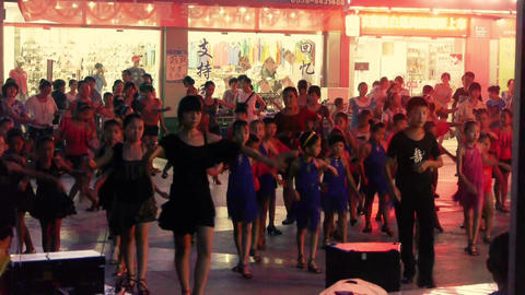 Dancing Chinese children crowd in the square at night Footage