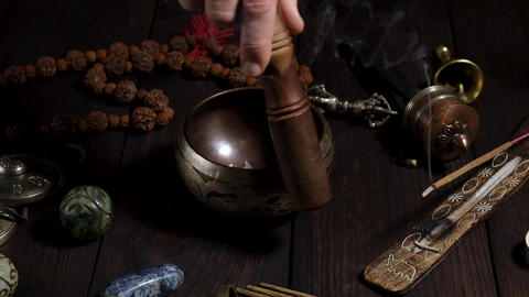 copper singing bowl and a man's hand leads a wooden stick over it Archivo