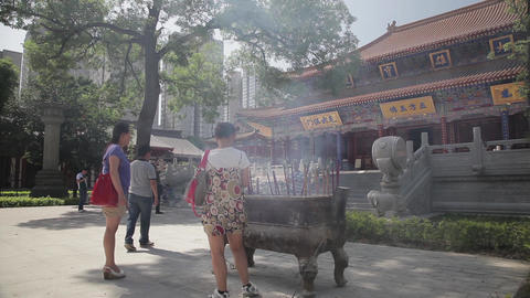 XI'AN, CHINA - MAY 24, 2012: Visitors burn incense and pray in Daxingshan Temple Live Action