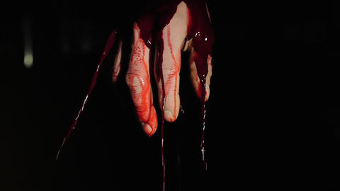 On the human hand, blood flows down against a dark background ビデオ