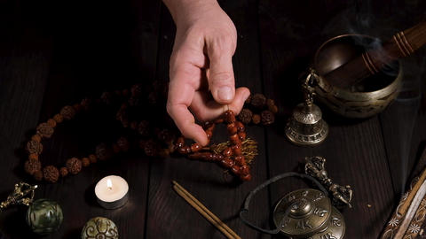 male hand holding a brown stone rosary, meditation and alternative medicine items on the table Archivo