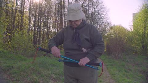 Elderly active woman with trekking poles Live Action