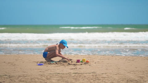 A little boy is playing in the sand on the sea, little... Stock Video Footage